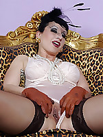 busty mature lady Trinity is wearing a glamorous outfit, heavy makeup and lots of jewelry. While smoking a cigarette she starts flashing her pussy underneath her wide satin skirt. She is shwoing off her brown stockings, satin lingerie and pops out her large tits while playing with her clit in her leather gloves